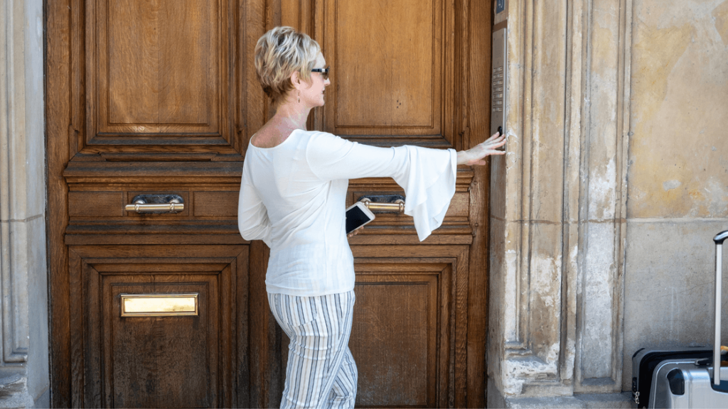 A woman calling a doorbell before renting an apartment in Paris